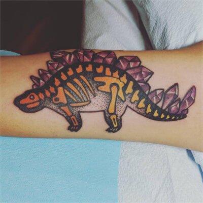 Colorful custom amethyst stegosaurus tattoo by Green Bay, WI tattoo artist Greg Counard