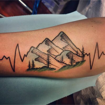 Colorful custom mountains tattoo on forearm by Green Bay, WI tattoo artist Greg Counard