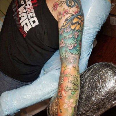 Colorful custom peacock themed sleeve tattoo by Green Bay, WI tattoo artist Greg Counard