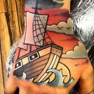 Colorful custom nautical ship tattoo on hand by Green Bay, WI tattoo artist Greg Counard