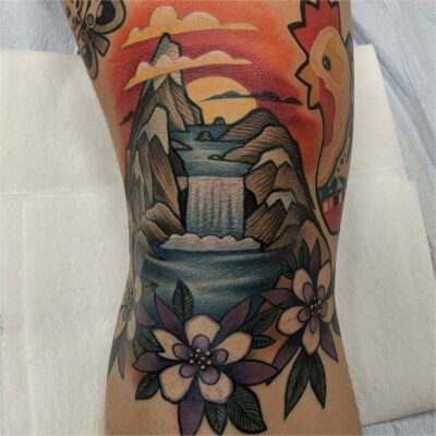Colorful custom waterfall and mountains tattoo by Green Bay, WI tattoo artist Greg Counard