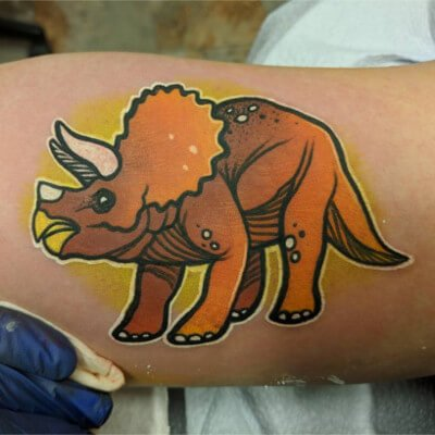 Colorful custom triceratops tattoo by Green Bay, WI tattoo artist Greg Counard